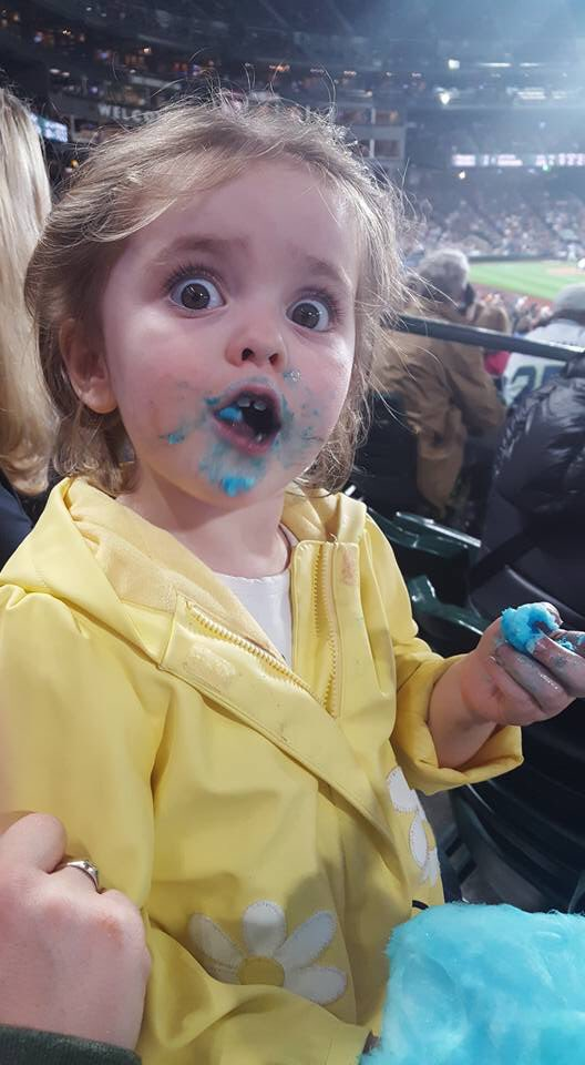 cute 3-year old making faces after eating cotton candy